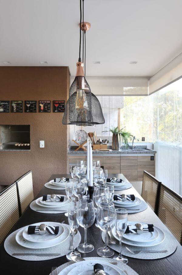 Churrasqueira pequena na varanda gourmet com mesa de jantar de madeira retangular para 8 lugares