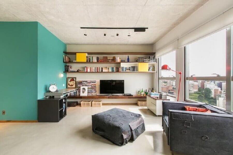 Cor de tinta azul ciano para parede de sala decorada com prateleiras de madeira Foto DT Estúdio Arquitetura