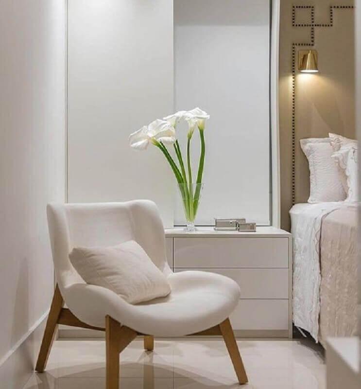 Cores neutras para quarto decorado com poltrona branca e luminária de parede Foto Decor Fácil