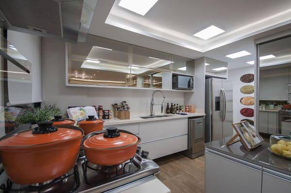 Cozinha branca com armário aéreo de vidro reflecta