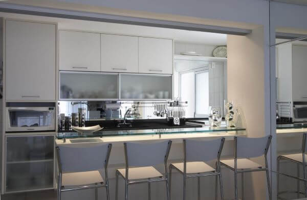 Cozinha com armário de vidro para copos e pratos organizados