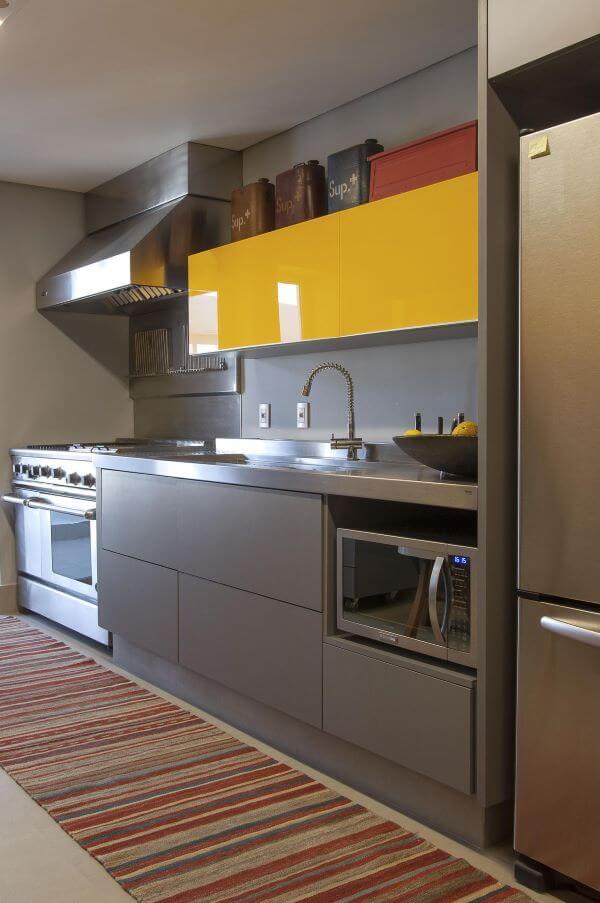 Cozinha com bancada e eletrodomésticos cor prata de inox e armário amarelo