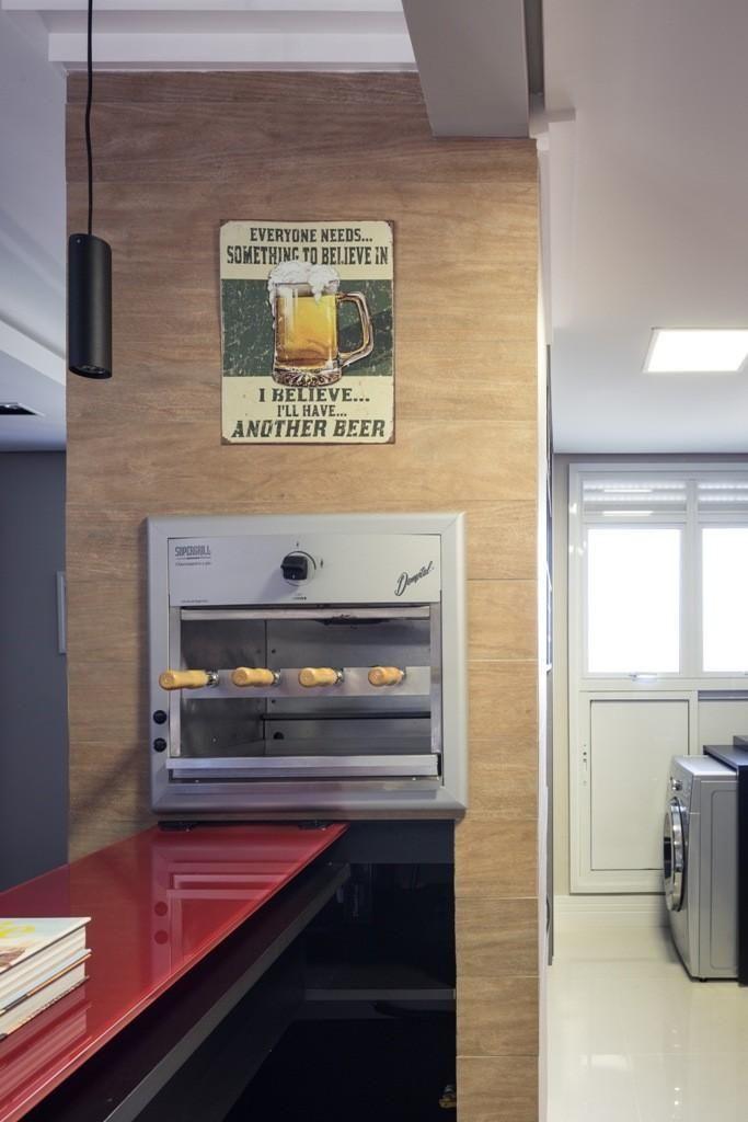 Cozinha com churrasqueira embutida perto da bancada vermelha