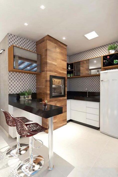 Cozinha com churrasqueira pequena com revestimento de madeira e granito