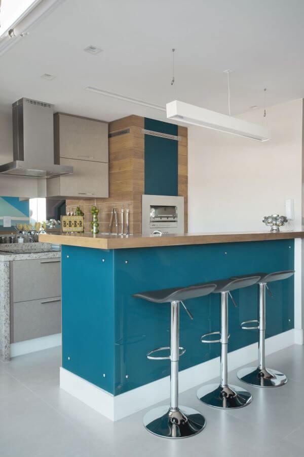 Cozinha com churrasqueira pequena revestida de madeira e tinta azul