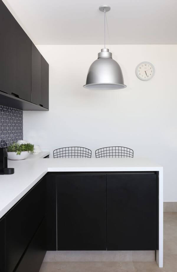 Cozinha em preto e branco com lustre na cor prata