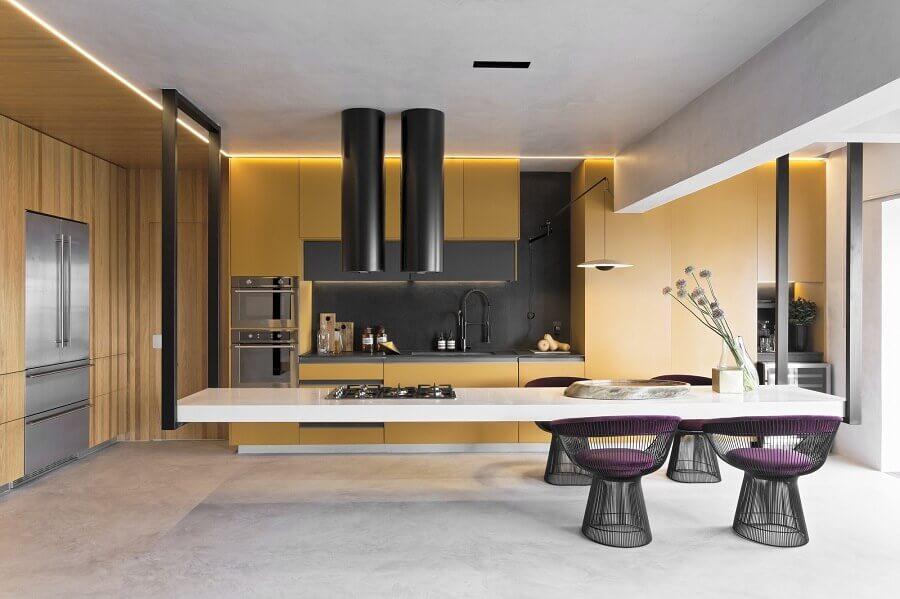 Cozinha planejada com ilha moderna decorada com armários amarelos e cadeira estofada Foto Diego Revollo
