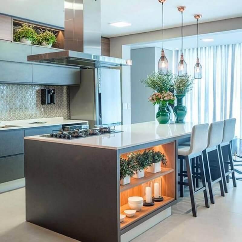 Cozinha planejada com ilha moderna decorada com luminária de vidro e nichos com iluminação Foto Houzz