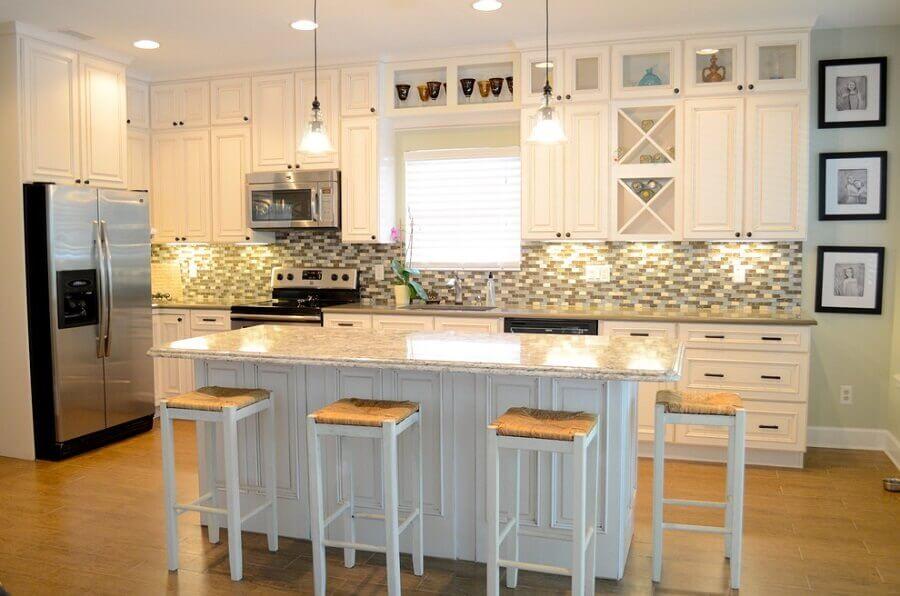 Cozinha planejada com ilha no meio decorada em estilo clássico Foto Beach home makeover