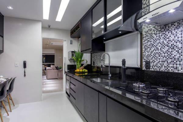 Cozinha preta planejada com armário de vidro