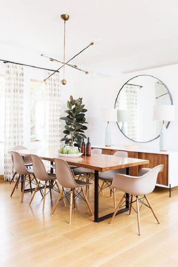 Decoração clean com lustre moderno e espelho redondo na sala de jantar Foto MyDomaine