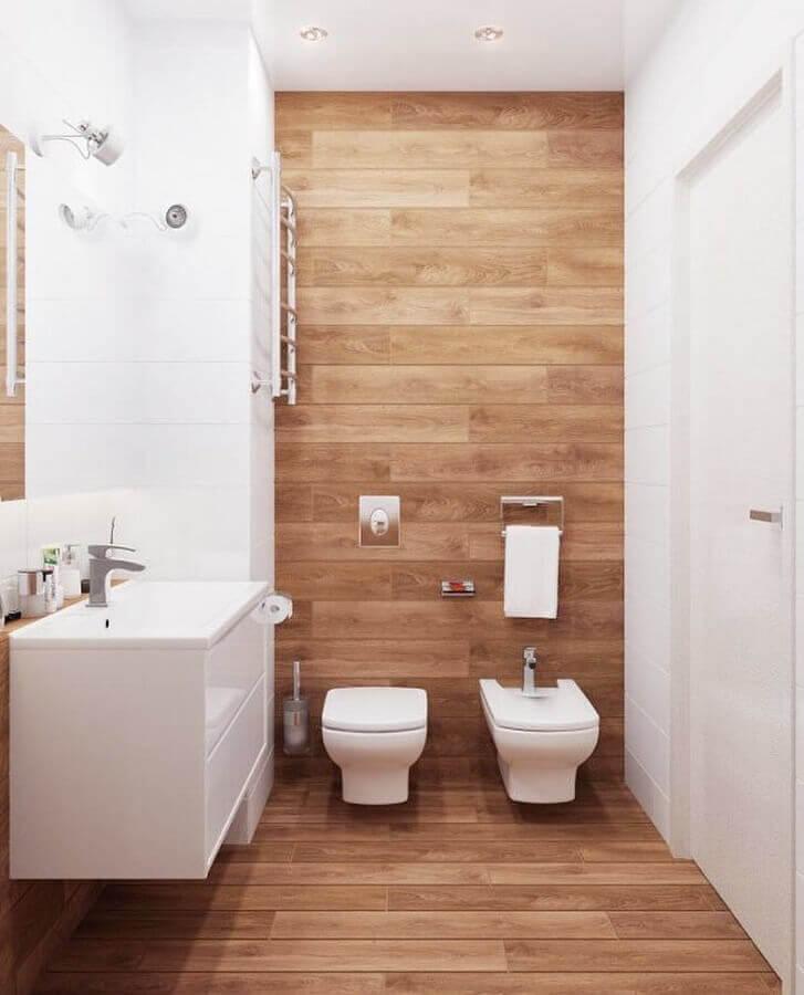 Decoração clean para banheiro com piso de madeira e gabinete branco pequeno Foto Decor Fácil