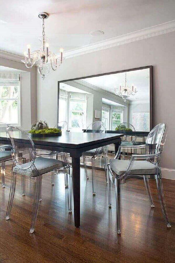 Decoração com cadeira transparente e espelho na sala de jantar Foto Anthropologie