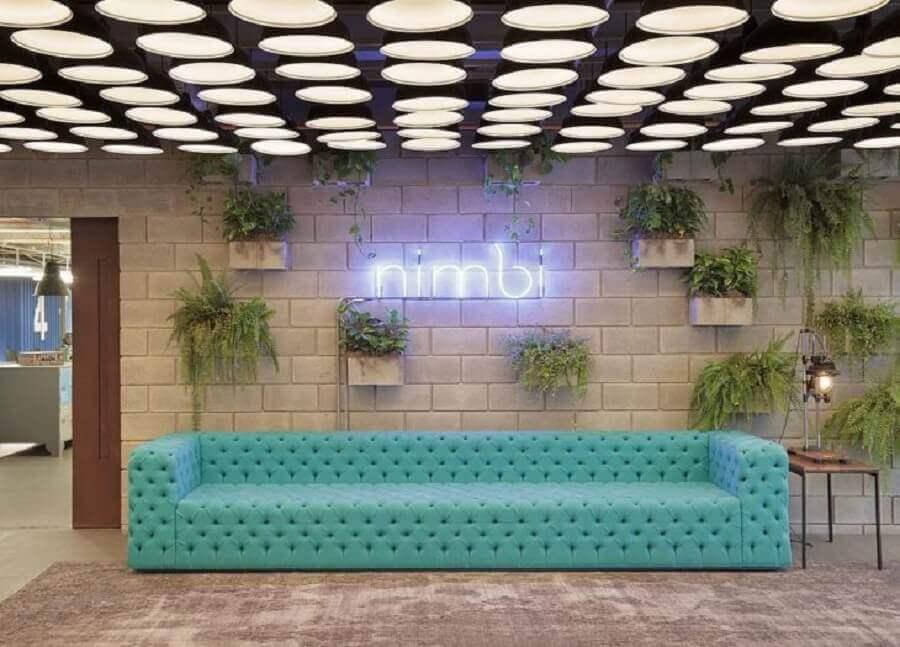 Decoração com vasos de plantas na parede e sofá cor ciano capitonê Foto Melina Romano Interiores
