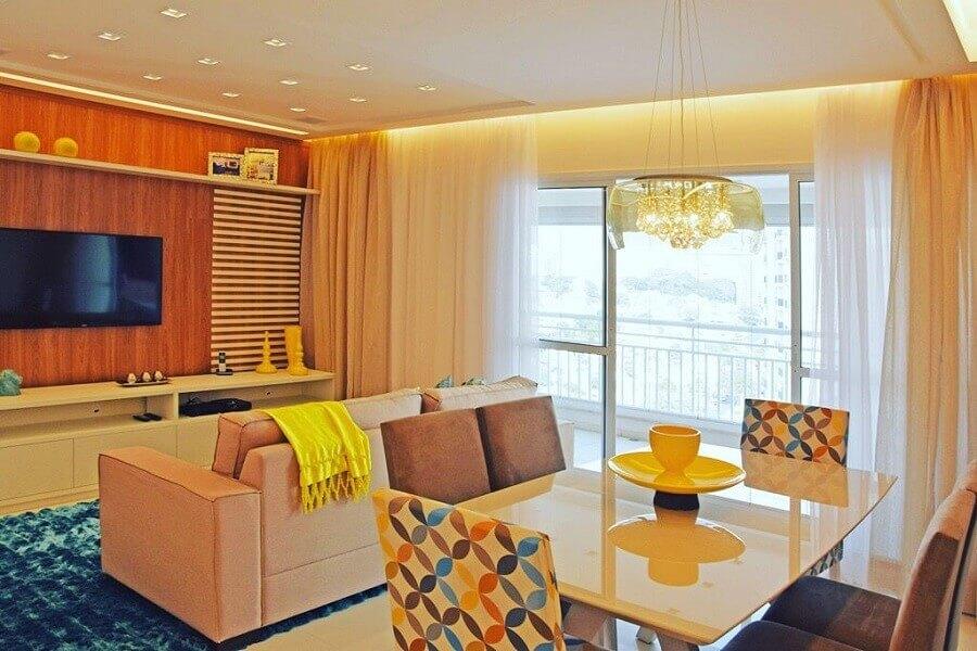 Decoração de apartamento com tapete azul e cadeiras coloridas para sala de estar e jantar integrada Foto Carlos Franscisco