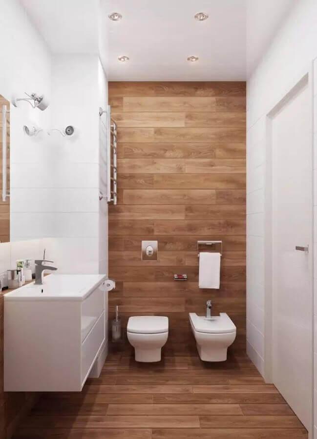 Decoração de banheiro com piso de madeira e gabinete branco pequeno Foto Valeru Anka