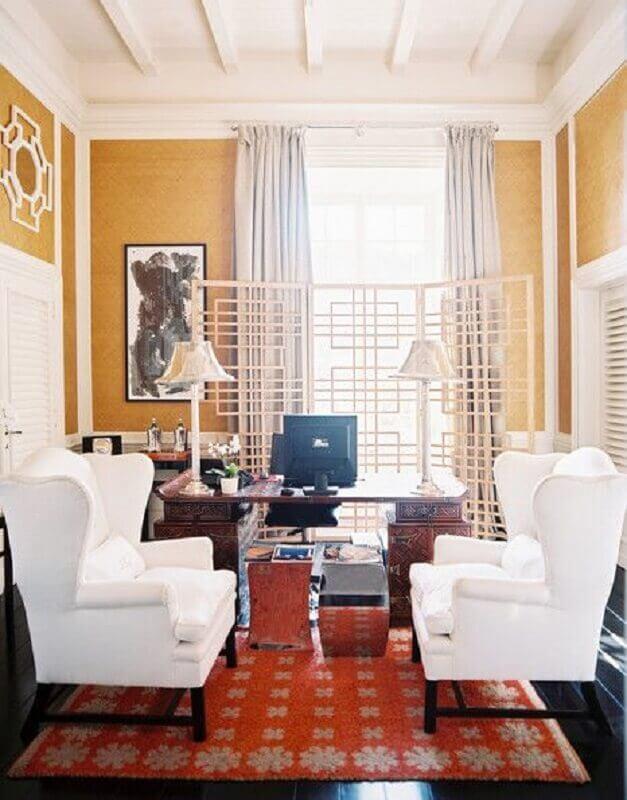 Decoração de escritório com parede amarela e poltrona branca Foto Lonny Magazine