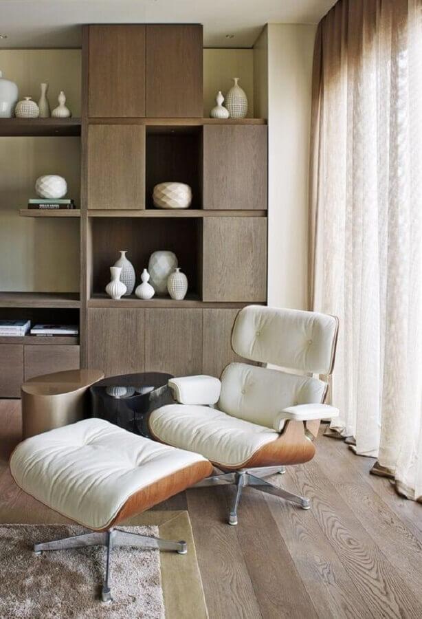 Decoração de sala com estante de madeira e poltrona eames branca Foto Architectural Digest