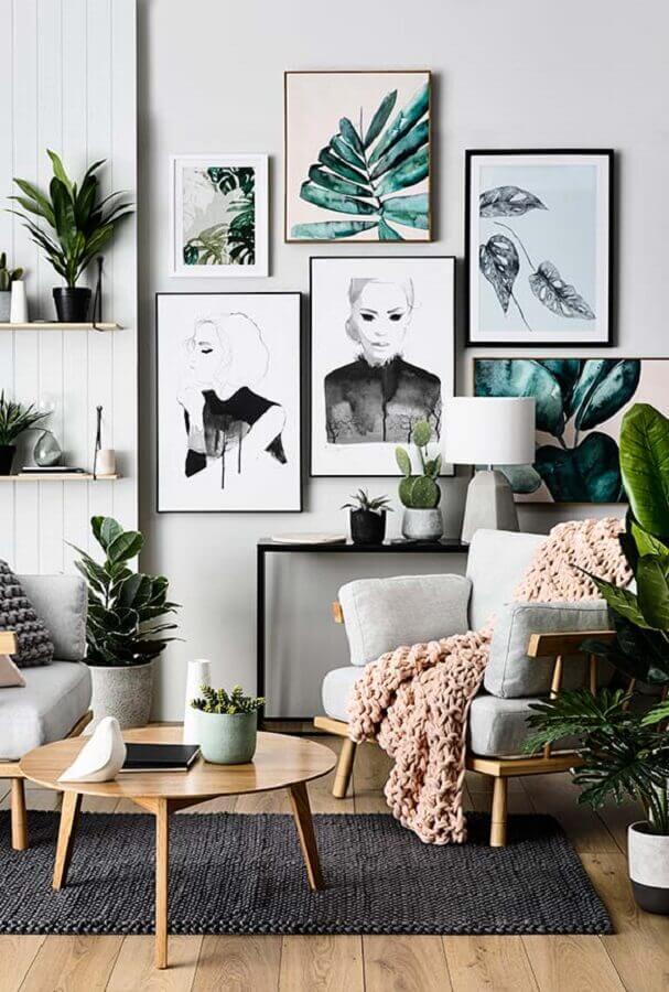 Decoração de sala com plantas e quadros de parede em cores claras Foto Decorie