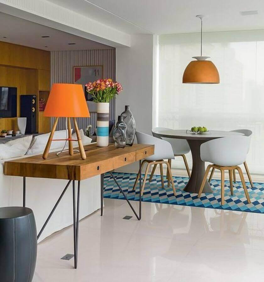 Decoração de sala de estar e jantar integrada com aparador de madeira e luminária redonda Foto Casa Pensada
