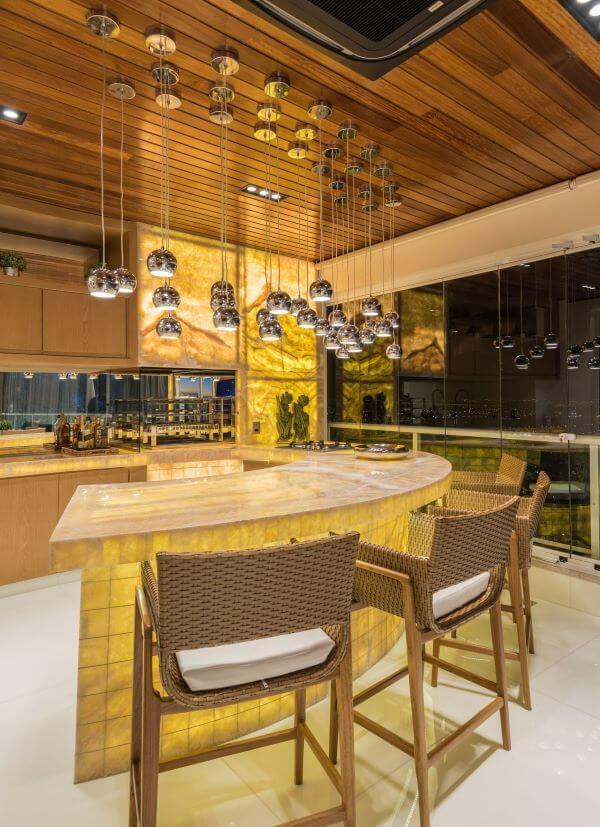 Decoração moderna com churrasqueira de parede e luminárias na bancada