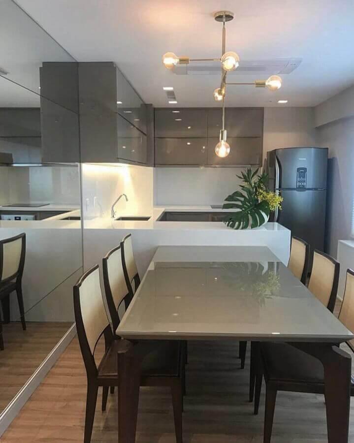 Decoração moderna em tons de cinza para sala e cozinha americana integradas com mesa planejada junto a bancada Foto Manuela Senna Arquitetura