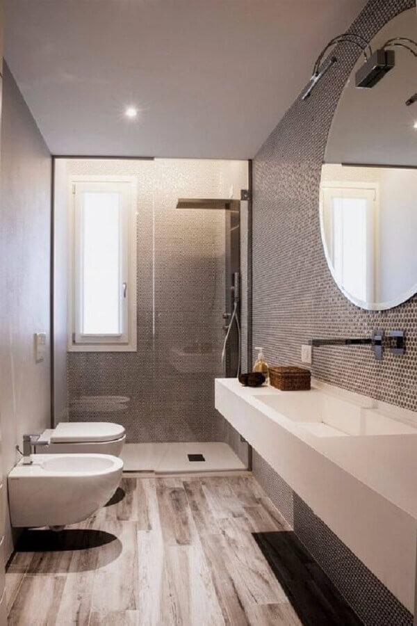 Decoração moderna para banheiro com piso de madeira e espelho redondo bisotado Foto Voglia di Ristrutturare