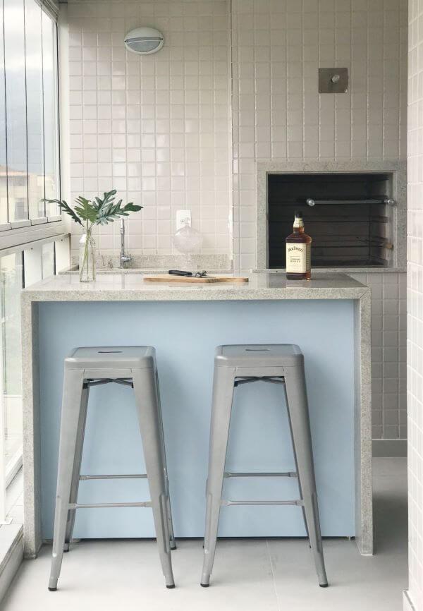 Espaço para churrasqueira pequena embutida e balcão de granito cinza para duas banquetas