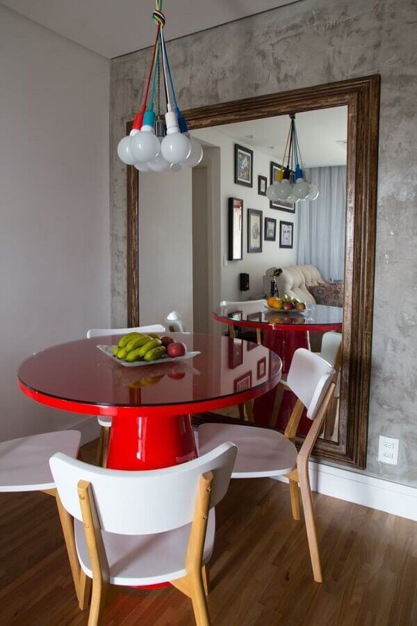 Espelho grande na sala de jantar decorada com mesa redonda vermelha e parede de cimento queimado Foto Decor Fácil