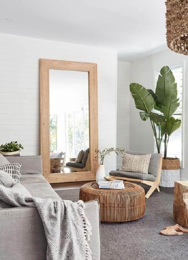 Espelho na sala de estar cinza e branca decorada com poltrona de madeira e vaso de planta no chão Foto Apartment Therapy