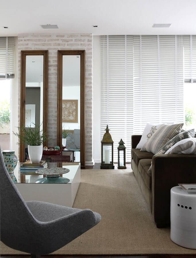Espelho na sala de estar grande decorada com sofá marrom e parede tijolinho Foto Caroline Gabriades