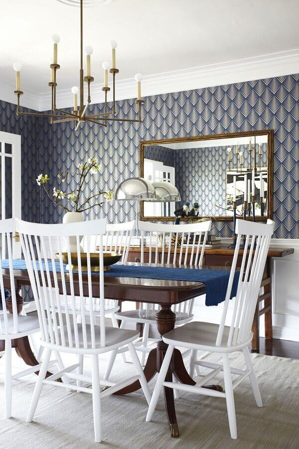 Espelho na sala de jantar decorada com papel de parede azul e cadeiras brancas Foto Home Furniture