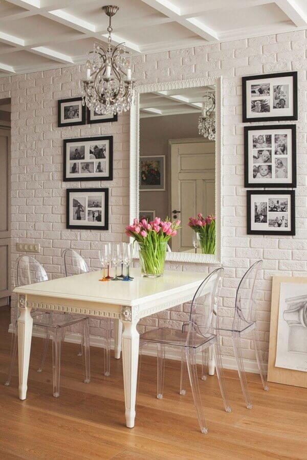 Espelho na sala pequena decorada com parede tijolinho branca e cadeiras transparentes Foto FresHOUZ