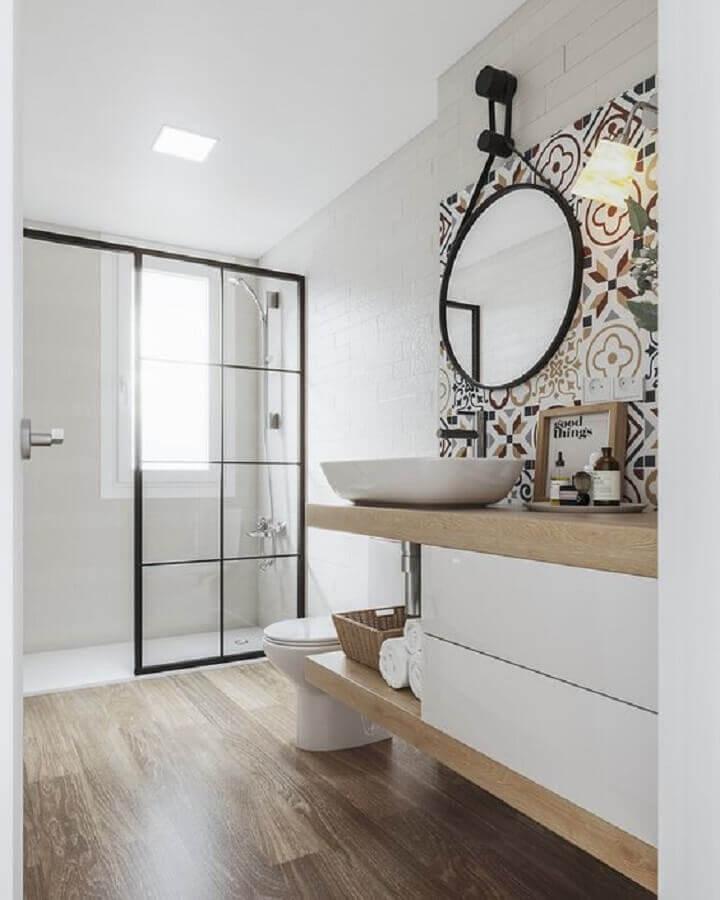 Espelho redondo e ladrilho hidráulico para decoração de banheiro com piso de madeira Foto Iglu Estúdio