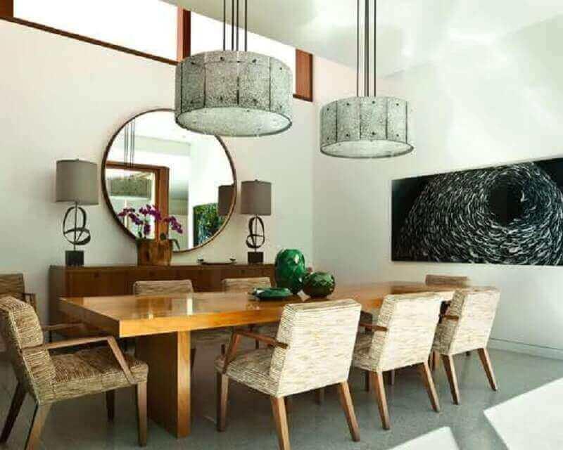 Espelho redondo na sala de jantar decorada com cadeira estofada e mesa grande de madeira Foto Home Furniture