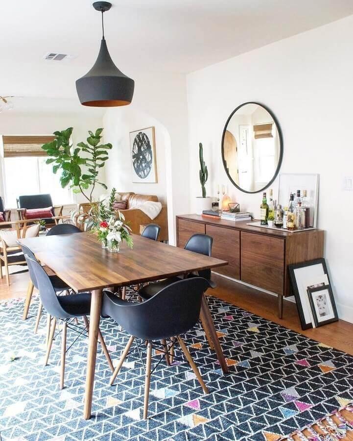 Espelho redondo na sala de jantar decorada com tapete preto e buffet de madeira Foto LIV Decora