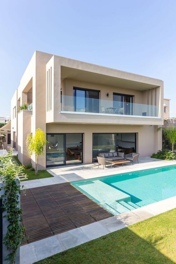 Fachada com guarda corpo de vidro e piscina moderna