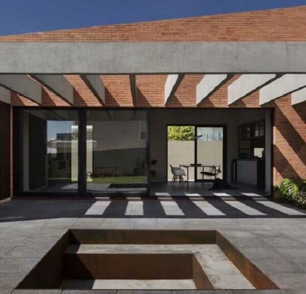 Fachada com pergolado de concreto na parede de tijolinho. Fonte: Decor Fácil