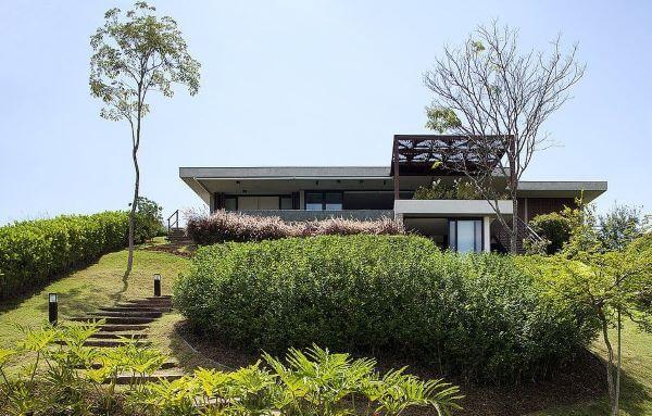 Fachada de casa de vidro com jardim na entrada
