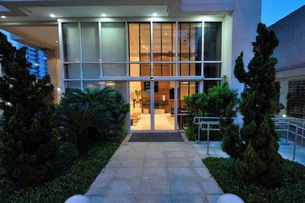 Fachada de casa de vidro com portas de vidro e persiana de aluminio preta para garantir a privacidade