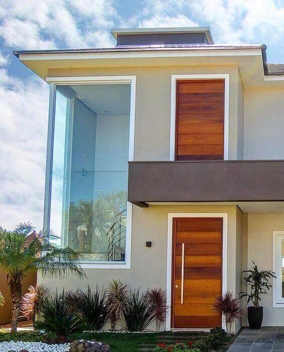 Fachada de vidro com porta de madeira