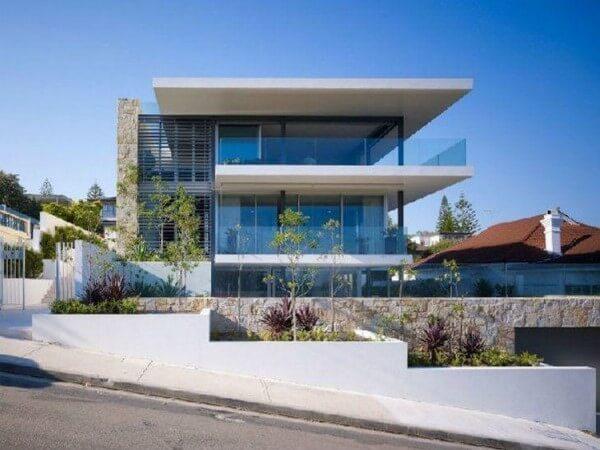 Fachada de vidro moderna com espaço para plantas na entrada