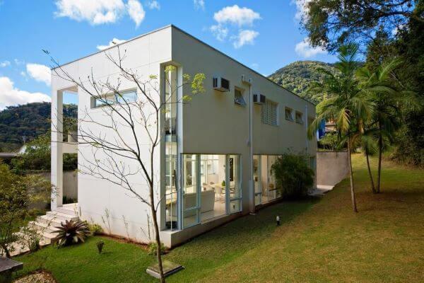 Fachada de vidro para casa com jardim amplo e design moderno