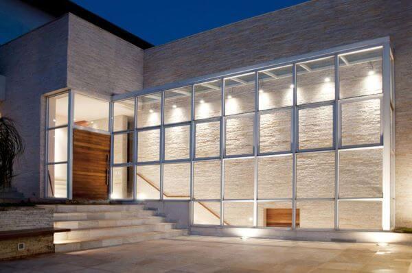 Fachada de vidro transparente com porta de madeira