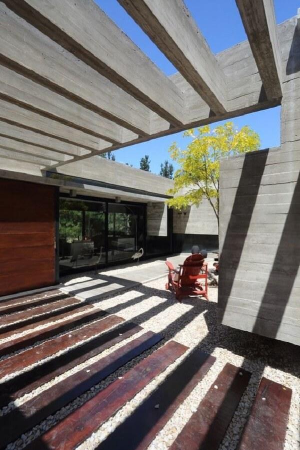 Garagem com pergolado de concreto e piso de pedras. Fonte: ArchDaily
