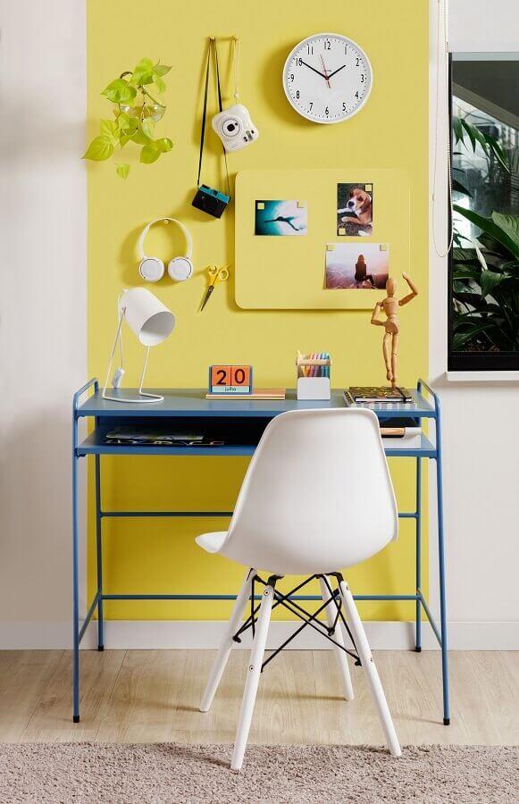 Home office decorado com parede amarela e escrivaninha azul simples Foto Tok&Stok