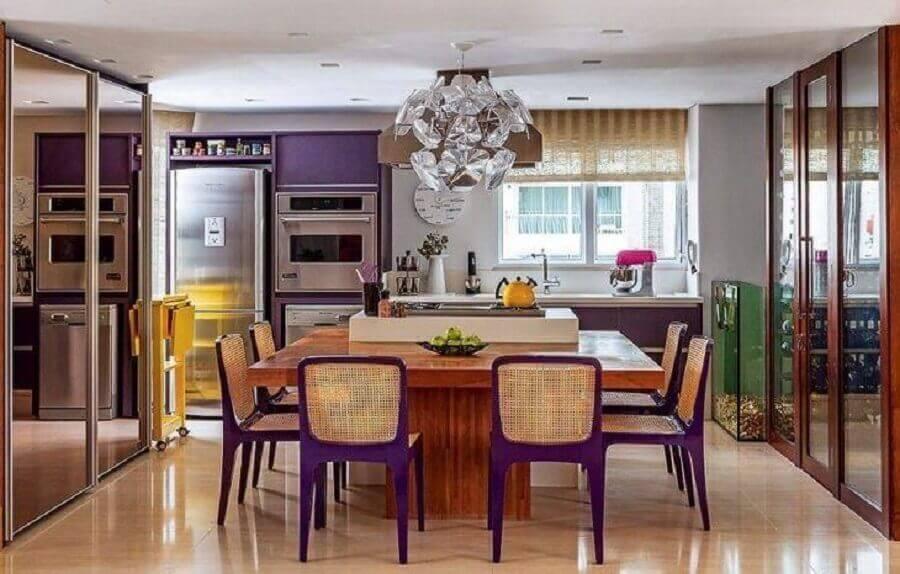 Lustre moderno para decoração de cozinha planejada com ilha e bancada de madeira com cadeiras roxas Foto Maricy Borges
