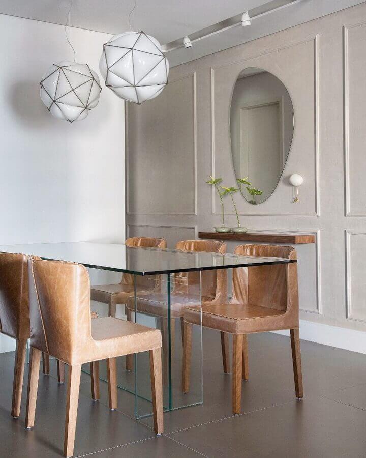 Modelo diferente de espelho na sala de jantar decorada com mesa de vidro e cadeiras de couro Foto FPR Studio