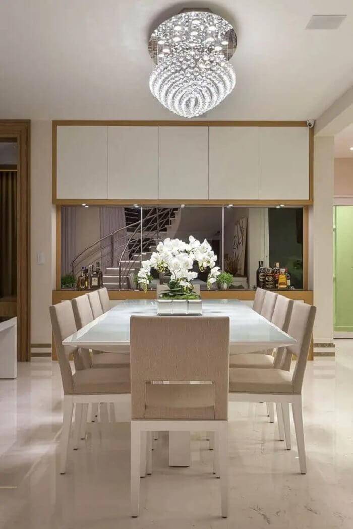 Modelo diferente de pendentes para sala de jantar de cristal toda branca com parede espelhada. Fonte: Iara Kilaris