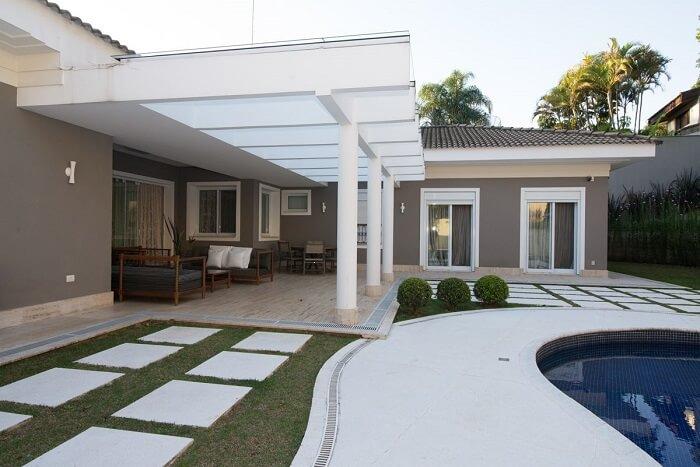 O pergolado de concreto com vidro traz charme para a área externa. Fonte: Riabitare